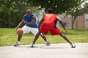Two men playing basketball for exercise